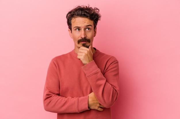 疑わしいと懐疑的な表情で横向きに見えるピンクの背景に孤立した若い白人男性。