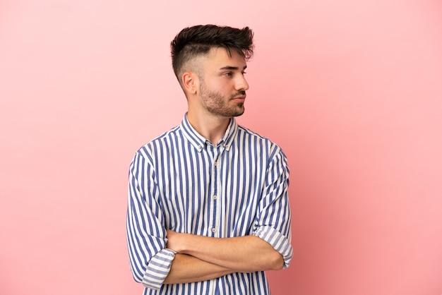 Молодой кавказский человек изолирован на розовом фоне, глядя в сторону