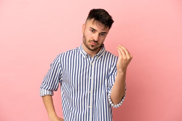 イタリアのジェスチャーを作るピンクの背景に分離された若い白人男性