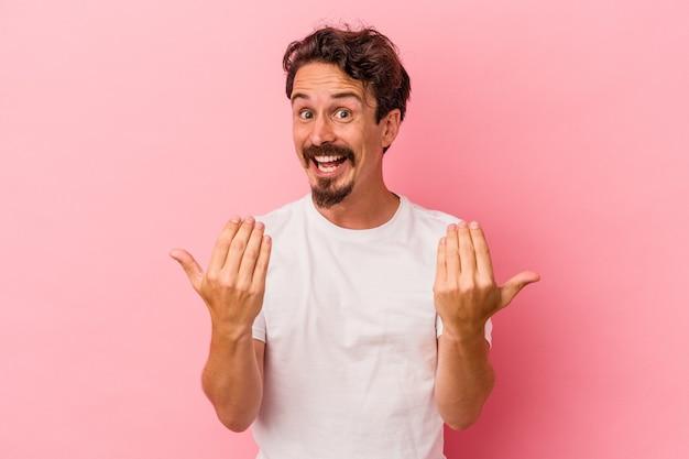 ピンクの背景に孤立した若い白人男性が、誘うように指であなたを指さします。