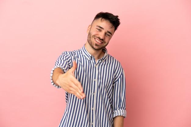 Молодой кавказский мужчина изолирован на розовом фоне, пожимая руку для заключения хорошей сделки