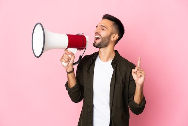 측면 위치에서 뭔가를 발표하기 위해 확성기를 통해 외치는 분홍색 배경에 고립 된 젊은 백인 남자