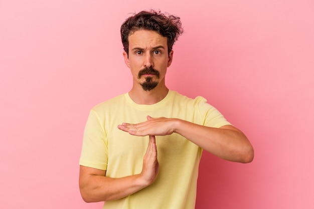 タイムアウトジェスチャーを示すピンクの背景に分離された若い白人男性。