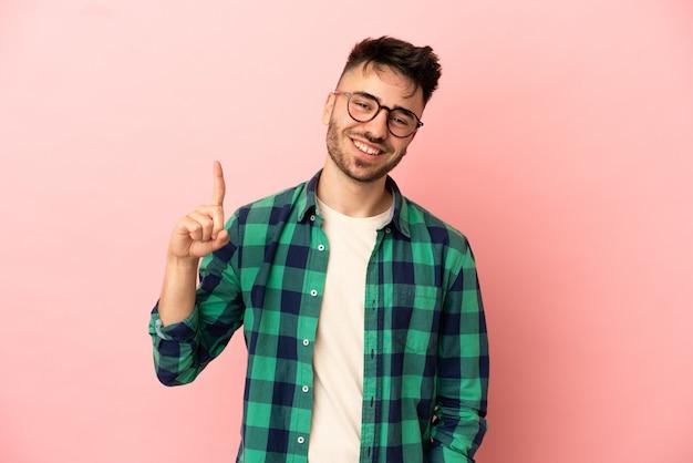 Молодой кавказский человек изолирован на розовом фоне, показывая и поднимая палец в знак лучших