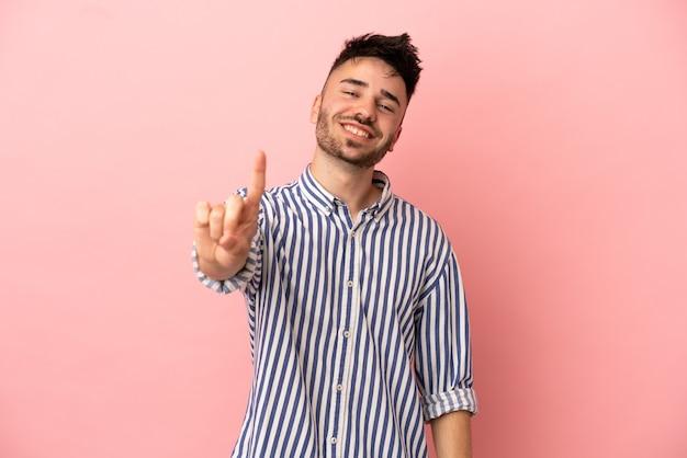 ピンクの背景に分離された若い白人男性が指を見せて持ち上げる