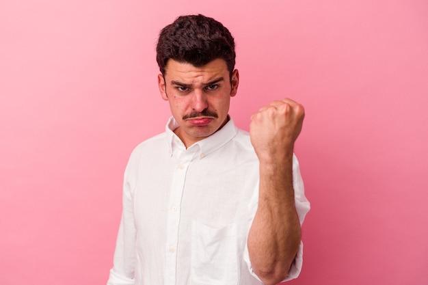 Молодой кавказский человек изолирован на розовом фоне, показывая кулак на камеру, агрессивное выражение лица.