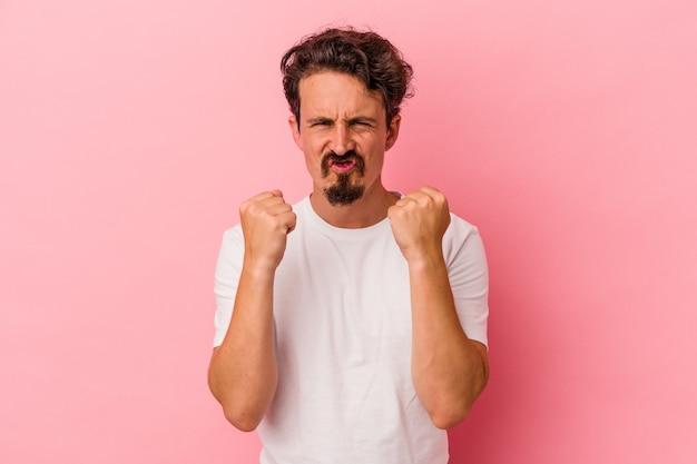 카메라에 주먹을 보여주는 분홍색 배경에 고립 된 젊은 백인 남자, 공격적인 표정.