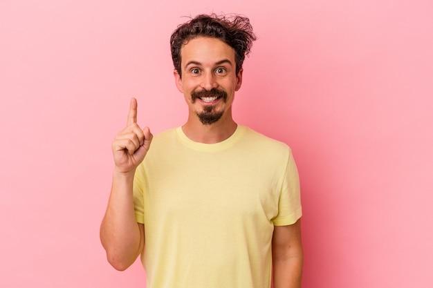 指でナンバーワンを示すピンクの背景に分離された若い白人男性。