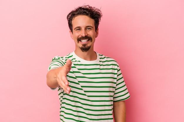 ピンクの背景に分離された若い白人男性笑顔と親指を上げる