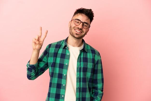 Молодой кавказский человек изолирован на розовом фоне улыбается и показывает знак победы