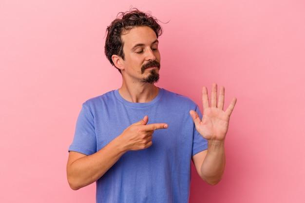 ピンクの背景に分離された若い白人男性は、指で5番を示して陽気に笑っています。