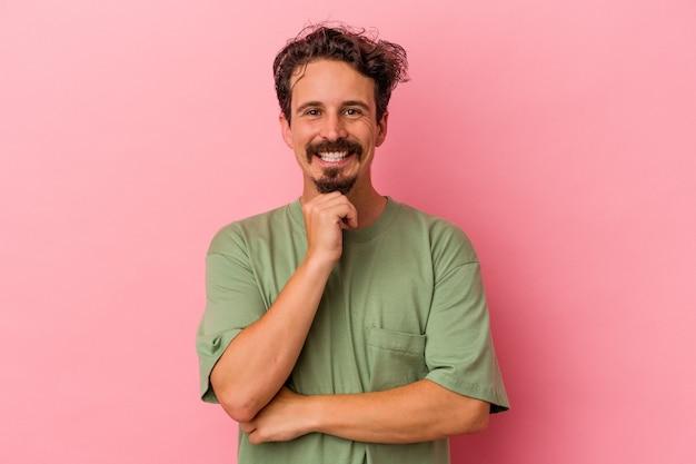 ピンクの背景に孤立した若い白人男性は、幸せと自信を持って笑って、手で顎に触れます。