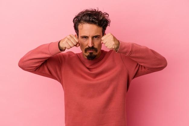 Молодой кавказский человек, изолированные на розовом фоне, бросает удар, гнев, борется из-за спора, бокс.