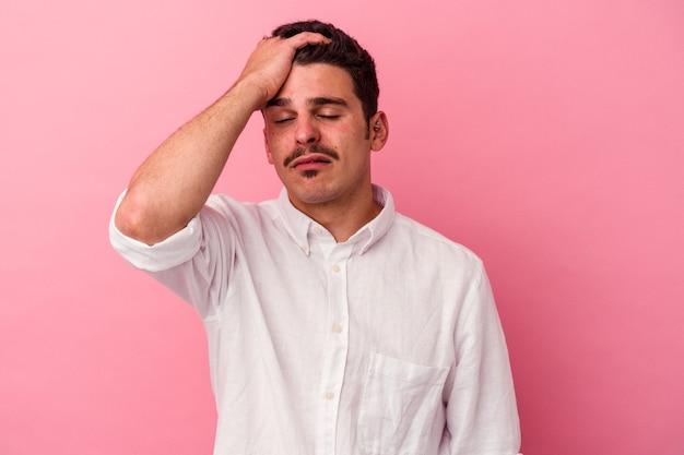 Молодой человек кавказской изолирован на розовом фоне устал и очень сонный, держа руку на голове.