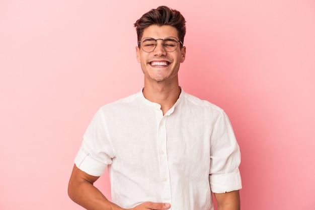 ピンクの背景に分離された若い白人男性はおなかに触れ、優しく微笑んで、食事と満足の概念。