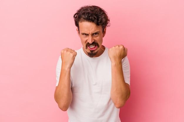 ピンクの背景に孤立した若い白人男性は、緊張した手で叫んで動揺します。