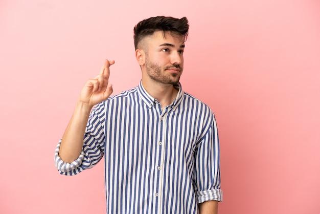 指が交差し、最高を願ってピンクの背景に分離された若い白人男性