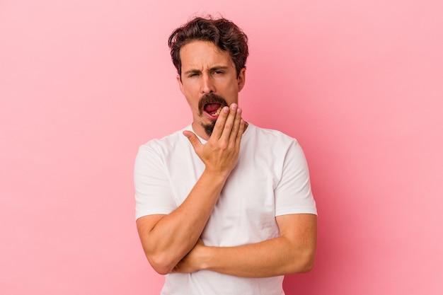 手で口を覆う疲れたジェスチャーを示すあくびをしているピンクの背景に分離された若い白人男性。