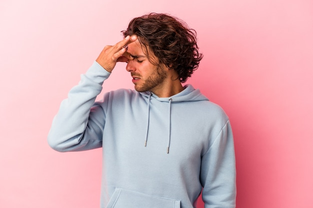 顔の正面に触れて、頭痛を持っているピンクのbakcgroundに孤立した若い白人男性。