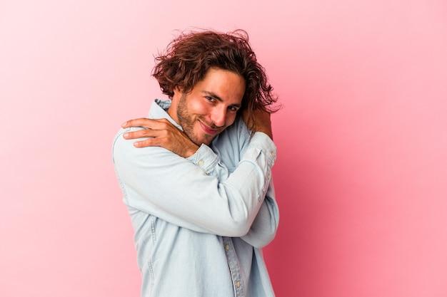 분홍색 bakcground 포옹에 고립 된 젊은 백인 남자 평온 하 고 행복 하 게 웃 고.