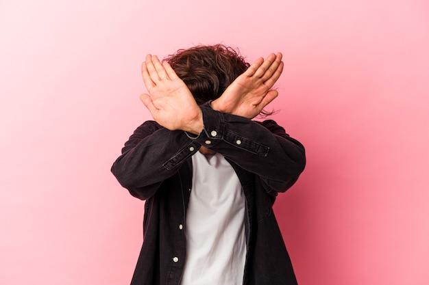 Молодой кавказский человек изолирован на розовом bakcground, держа скрещенными руками, концепцию отрицания.