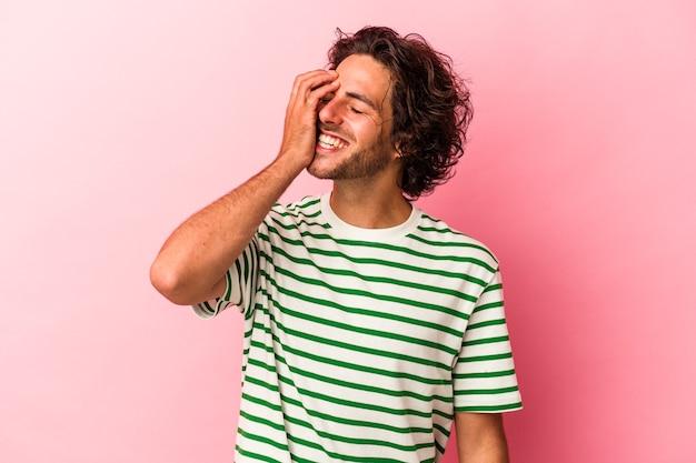 분홍색 bakcground에 고립된 젊은 백인 남자는 행복하고 평온하며 자연스러운 감정을 웃고 있습니다.