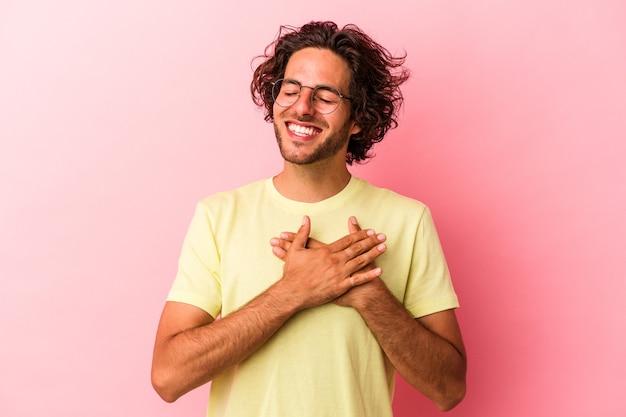 ピンクのbakcgroundに孤立した若い白人男性は、心に手を置いて笑って、幸福の概念。