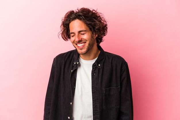 ピンクのbakcgroundに孤立した若い白人男性は笑って目を閉じ、リラックスして幸せを感じます。