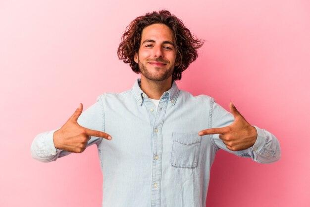 シャツのコピースペースを手で指しているピンクのbakcground人に孤立した若い白人男性、誇りと自信を持って