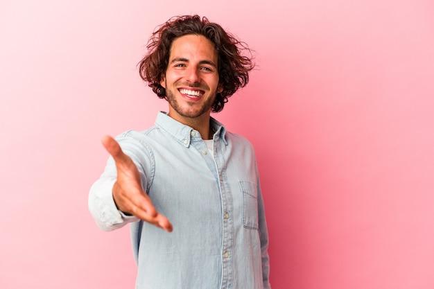 挨拶のジェスチャーでカメラに手を伸ばしてピンクのbakcgroundに分離された若い白人男性。
