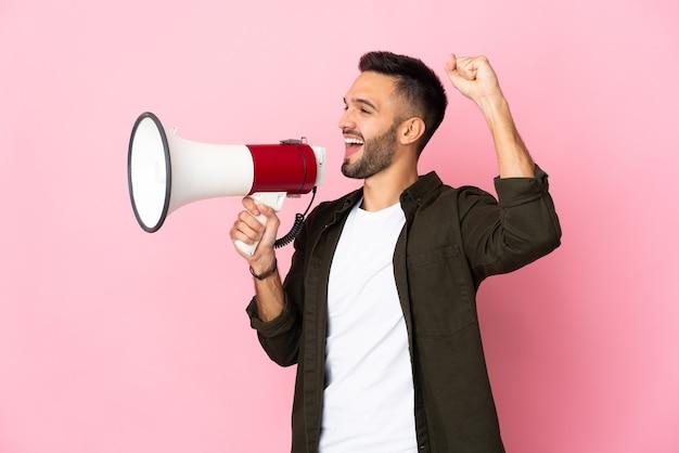 측면 위치에서 뭔가를 발표하기 위해 확성기를 통해 외치는 분홍색 벽에 고립 된 젊은 백인 남자