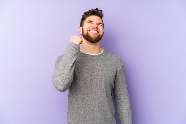 勝利、情熱と熱意、幸せな表現を祝う紫色の背景に孤立した若い白人男性。