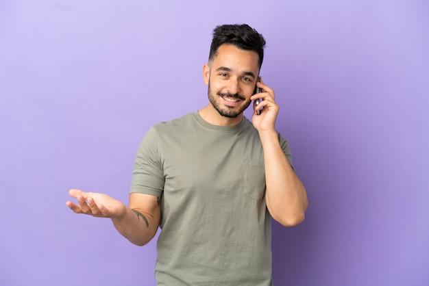 誰かと携帯電話で会話を続けている紫色の背景に孤立した若い白人男性