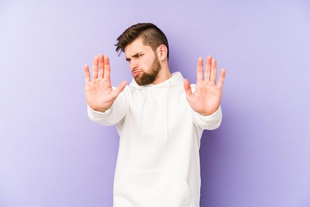 정지 신호를 보여주는 뻗은 손으로 서 보라색 배경에 고립 된 젊은 백인 남자, 당신을 방지.