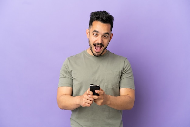 紫色の背景に孤立した若い白人男性は驚いてメッセージを送信します