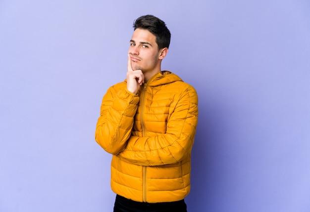 Молодой кавказский человек, изолированные на фиолетовом фоне, недоволен, глядя в камеру с саркастическим выражением лица.