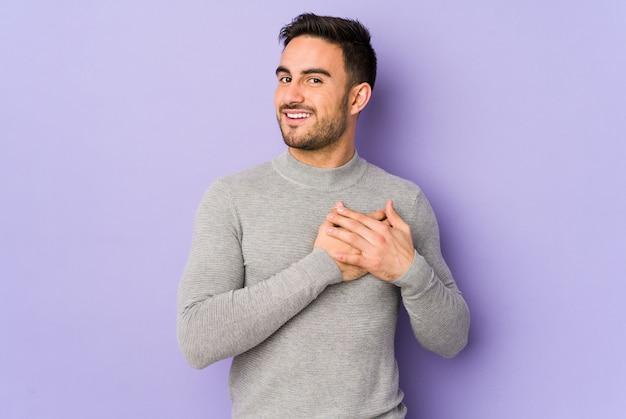 Молодой кавказский человек изолированный на пурпуре имеет дружелюбное выражение, отжимая ладонь к груди. концепция любви
