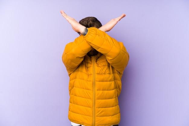 Молодой кавказский человек изолирован на фиолетовом скрещенных руках, концепция отрицания.