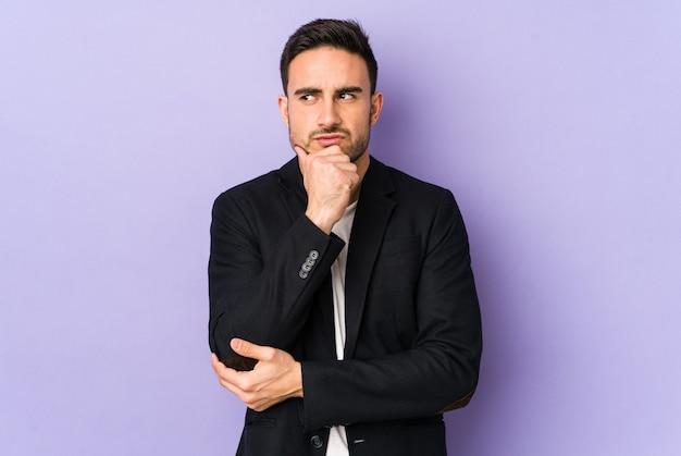 Молодой кавказский человек изолирован на фиолетовом, глядя в сторону с сомнительным и скептическим выражением лица.