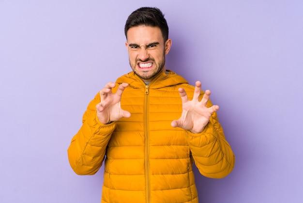 Молодой кавказский человек изолирован на фиолетовом, показывая когти, имитирующие кошку, агрессивный жест.