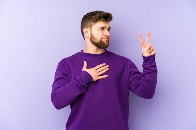Молодой кавказский человек изолирован на фиолетовом пространстве, принимая присягу, положив руку на грудь.
