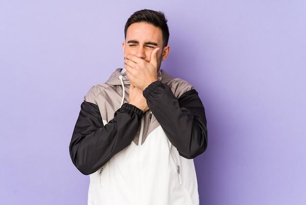 Молодой кавказский мужчина, изолированный на фиолетовом, страдает от боли в горле из-за вируса или инфекции.