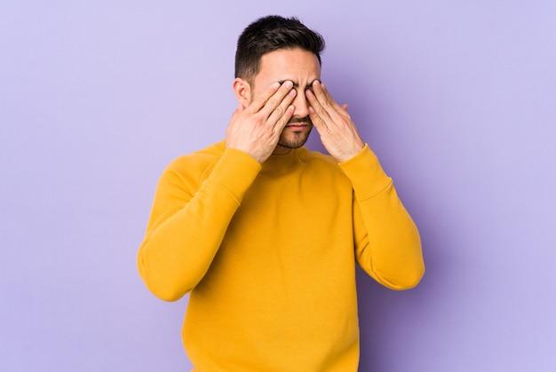 Молодой кавказский человек, изолированные на фиолетовой стене, боится, закрывая глаза руками.