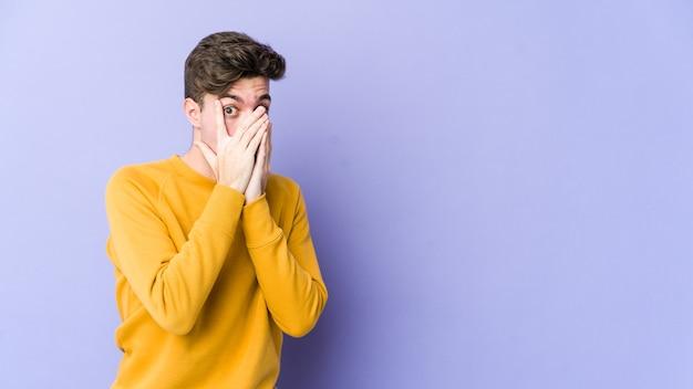Молодой кавказский человек, изолированный на фиолетовой стене, моргает сквозь пальцы испуганно и нервно.