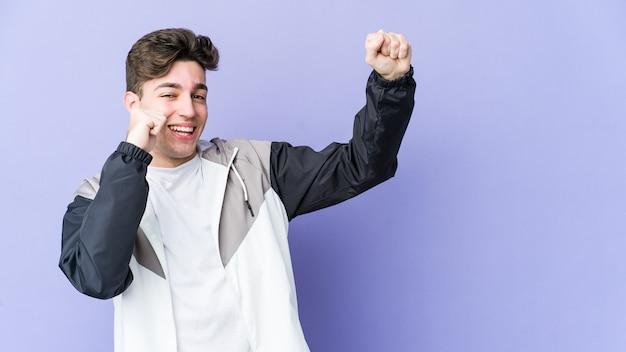 Молодой кавказский человек изолирован на фиолетовой стене, танцует и развлекается.