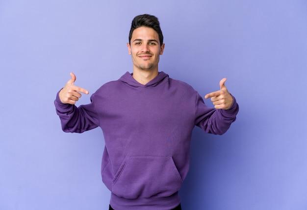 Молодой кавказский мужчина изолирован на фиолетовой стене человека, указывая рукой на пространство для копирования рубашки, гордый и уверенный