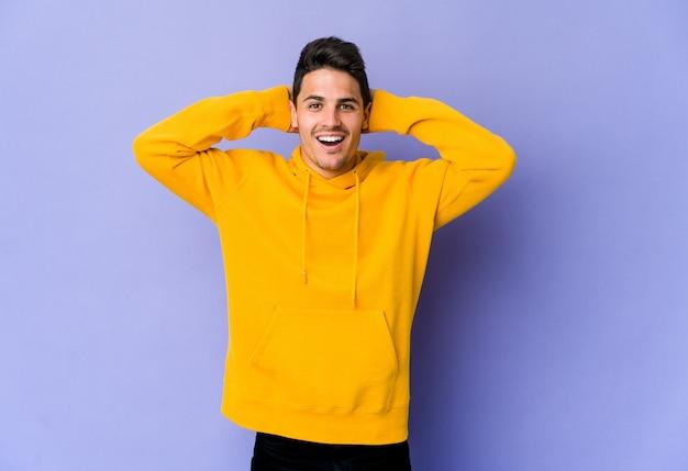 Молодой кавказский человек изолирован на фиолетовой стене кричит, очень взволнован, страстен, доволен чем-то.