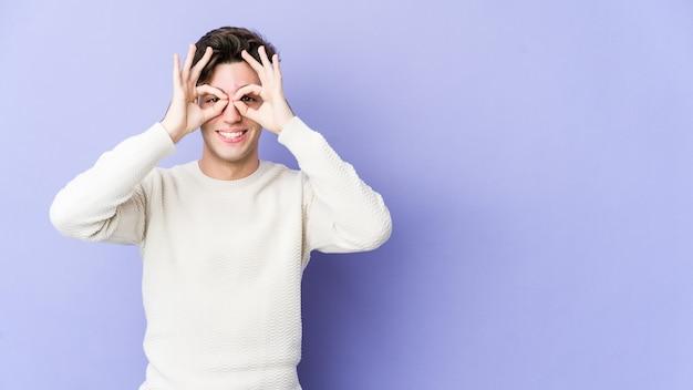 Молодой кавказский человек изолирован на фиолетовой стене, показывая хорошо знаком над глазами