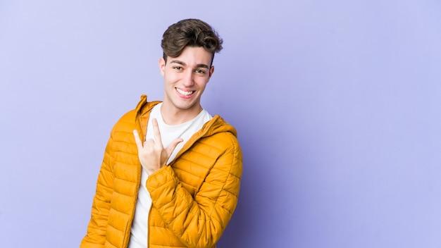 Молодой кавказский мужчина изолирован на фиолетовой стене, показывая рок-жест пальцами