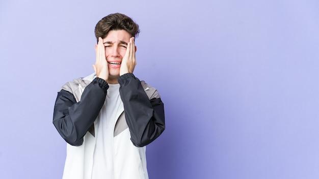 Молодой кавказский человек изолирован на фиолетовой стене нытья и безутешно плачет.